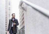 Homem de negócios sorridente com telefone celular e fones de ouvido em movimento, Nova York, EUA — Fotografia de Stock
