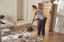 Woman vacuum cleaning carpet at home — Stock Photo
