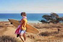 Молода людина, несучи для серфінгу на узбережжі — стокове фото