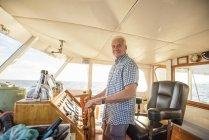 Confident senior man steering a boat — Stock Photo