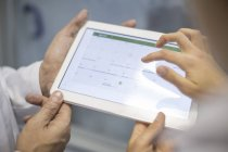 Cropped image of two scientists sharing tablet — Stock Photo