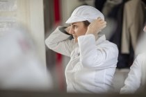 Cheese factory worker putting on protective clothes — Stock Photo