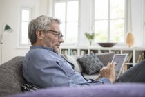 Mature man sitting on the sofa and using tablet at home — Stock Photo