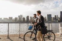 Deux hommes d'affaires à vélo marchant le long d'East River, New York, États-Unis — Photo de stock