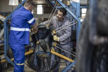 Two tire repairmen working together in factory — Stock Photo