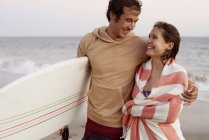 Smiling young couple on the beach carrying surfboard — Stock Photo