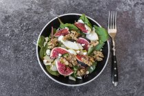 Bowl of salad with mangold, feta cheese, figs, pear and walnuts on grey stone surface with fork — Stock Photo