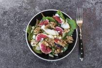 Чаша салат з Мангольд, сир фета, інжир, груші та волоські горіхи на сірий камінь поверхні з виделкою — стокове фото