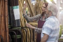 Shop assistent and client in garden centre looking at bamboo fencing — Stock Photo