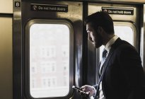 Young businessman taking metro, using smartphone — Stock Photo