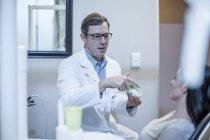 Professioneller kaukasischer Zahnarzt mit Zahnschimmel im Gespräch mit dem Patienten — Stockfoto
