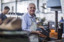 Sorridente calzolaio lavora sulla scarpa in officina — Foto stock