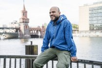 Germany, Berlin, laughing man wearing blue rainjacket sitting on railing in front of Oberbaum Bridge — Stock Photo