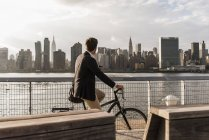 Businessman riding bicycle and looking at skyline of Manhattan, New York City, USA — Stock Photo