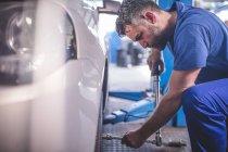 Meccanico di automobile in un workshop cambiare pneumatico — Foto stock