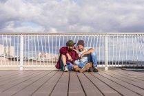 USA, New York City, two friends sitting on bridge on Coney Island and sharing headphones — Stock Photo