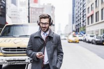 Sorrindo empresário com telefone celular e fones de ouvido em qualquer lugar, cidade de Nova Iorque, EUA — Fotografia de Stock