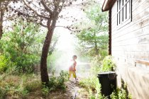 Little boy playing with garden hose — Stock Photo