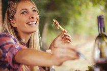 Lächelnde Frau, die tagsüber im Freien zu essen — Stockfoto