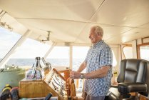 Homem idoso confiante dirigindo um barco — Fotografia de Stock