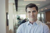 Retrato de jovem empresário em pé no cargo — Fotografia de Stock