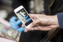 Handy-Foto von Tattoo-Künstler bei der Arbeit — Stockfoto