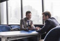 Zwei Geschäftsleute mit Mobiltelefonen auf dem Passagierdeck einer Fähre — Stockfoto