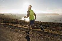 Young man running on the beach, france, crozon peninsula — Stock Photo