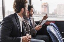 Двоє бізнесменів, спілкуючись на пасажирського салону поромі — стокове фото