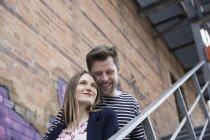 Sonriente pareja en escaleras, graffiti sobre pared de ladrillo - foto de stock