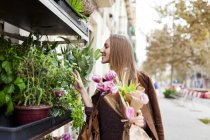 Smiling woman shopping for flowers — Stock Photo