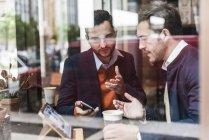 Бизнесмены, встреча в кафе и с помощью мобильных устройств — стоковое фото