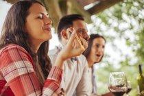 Женщина с друзьями ест на открытом воздухе — стоковое фото