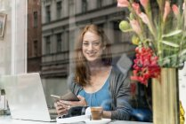 Portrait of smiling woman with smartphone and laptop in a coffee shop — Stock Photo