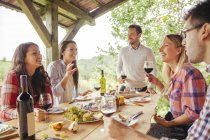 Friends socializing at outdoor table with red wine and cold snack — Stock Photo