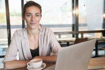 Портрет усміхнений молода жінка з чашкою кави і ноутбук в кафе — стокове фото