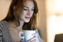 Portrait of smiling woman with cup of coffee using laptop — Stock Photo