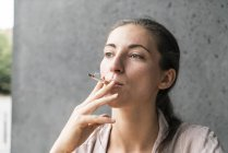 Portrait of smoking young woman — Stock Photo