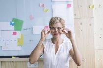 Lächelnde Geschäftsfrau vor Whiteboard im modernen Büro — Stockfoto
