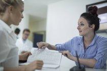 Due donne con libro alla reception in clinica — Foto stock