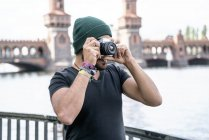 Germany, Berlin, man taking pictures with camera in front of Oberbaum Bridge — Stock Photo