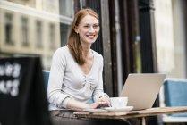 Рудоволосої жінка з ноутбука на тротуарі кафе — стокове фото