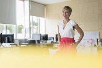 Sorrindo mulher de pé no escritório criativo — Fotografia de Stock