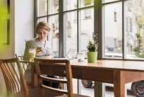 Young woman with cell phone and tablet in a cafe — Stock Photo