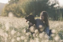 Young woman and her dog in field of flowers at twilight — Stock Photo