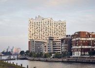 Germania, Amburgo, Hafencity, vista su Elbe Philharmonic Hall con case plurifamiliari in primo piano — Foto stock