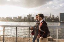 Deux jeunes hommes marchant le long d'East River, New York City, USA — Photo de stock
