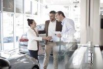 Autohändler schüttelt Frau im Autohaus die Hand — Stockfoto