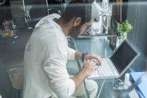 Joven, trabajando con el ordenador portátil de escritorio en una oficina moderna - foto de stock