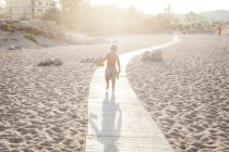 Back view of little boy walking on boardway on the beach at backlight — Stock Photo